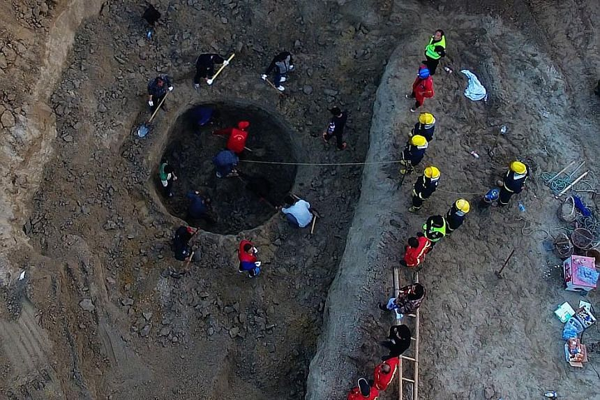 An excavator removing soil from around the mouth of the well in the Chinese city of Baoding as rescuers try to locate and extricate a six-year-old boy who had fallen in on Sunday.