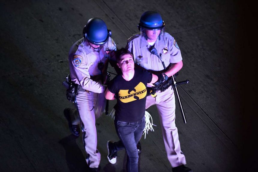 A protester who refused to leave a Los Angeles freeway is apprehended by California Highway Patrol officers.