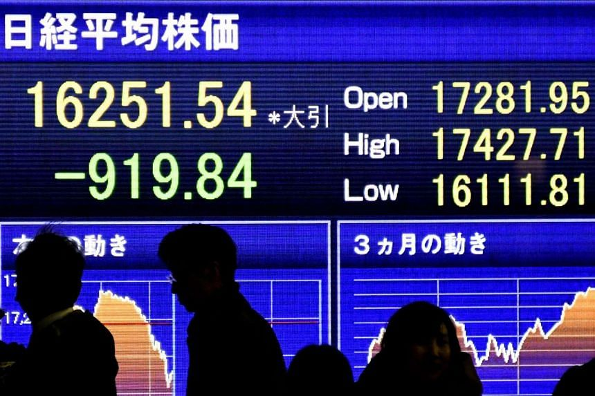 Pedestrians stand before a stock market indicator board in Tokyo.