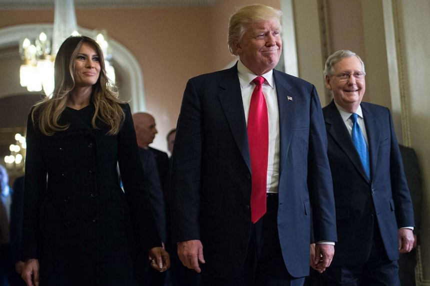 US President-elect Donald Trump and wife Melania walk with Senate Majority Leader Mitch McConnell (right) following a meeting at the Capitol.
