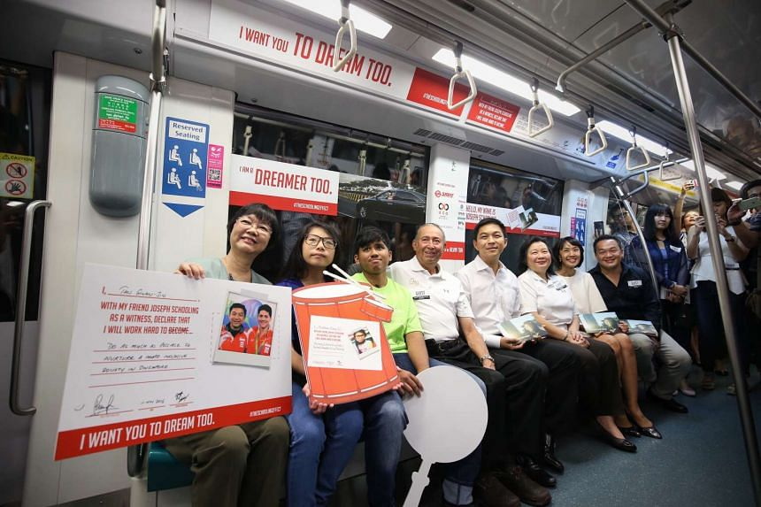 "Make-A-Wish Foundation Singapore CEO Judy Lim (far left) holding the pledge that was presented to her by Minister for Social and Family Development Tan Chuan-Jin (fifth from left) at the ""Hello, My Name is Joseph Schooling"" concept train launch on Fr"