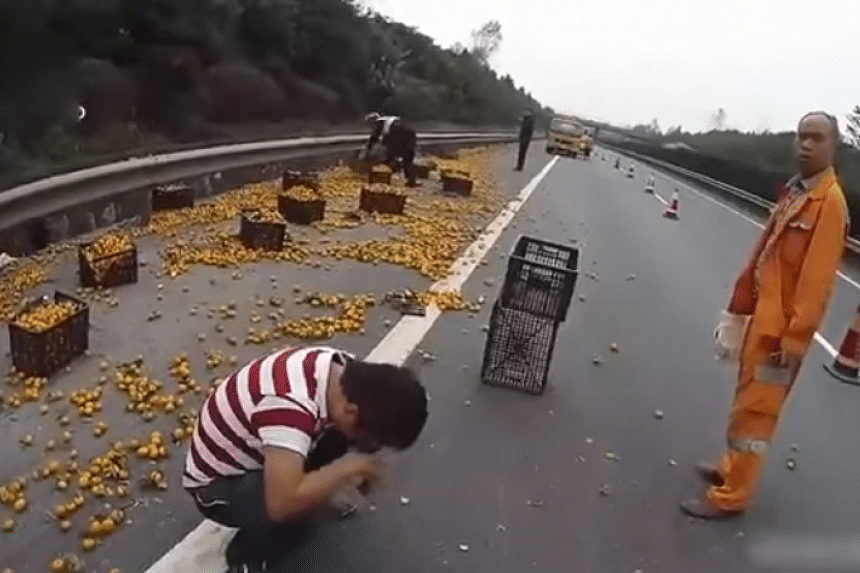 A Chinese driver wept at the roadside as villagers looted oranges after his truck overturned.