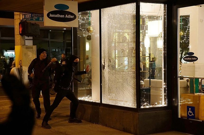 Demonstrators breaking a shop window during a protest in Portland, Oregon, yesterday against the election of Mr Trump as US President. Part of the reason for Mr Trump's historic win on Wednesday was his promise to bring back jobs to America, which he