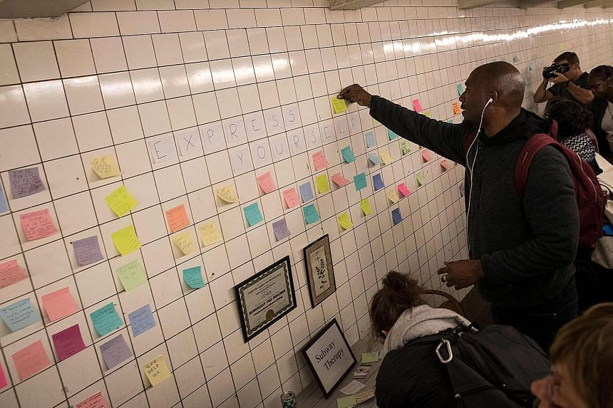 Commuters using Post-it notes to share their thoughts and pen messages, many of which were politically themed, in New York City's Sixth Avenue subway station on Thursday, as part of a public art project called Subway Therapy. Artist Matthew Chavez cr