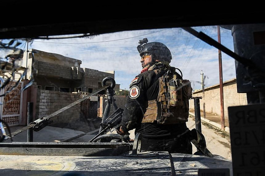 A member of the Iraqi forces patrolling a village at Mosul's edge, as clashes go on between the Iraqi military and ISIS.