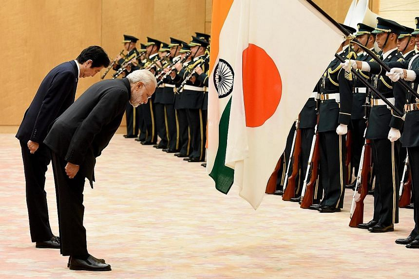 Japanese PM Abe and visiting Indian PM Modi bowing before the two countries' national flags at a review of the honour guard yesterday in Tokyo.