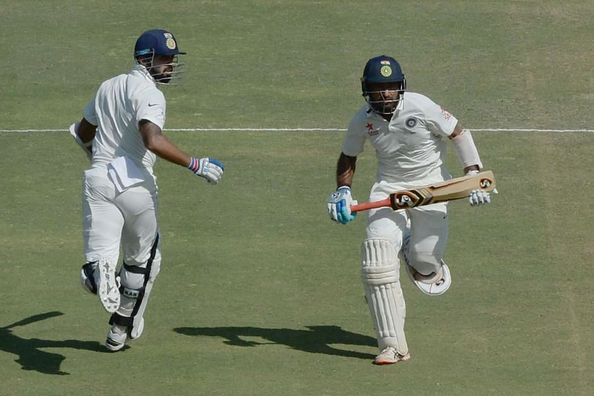 India's Murali Vijay (left) and Cheteshwar Pujara run between the wickets on the third day of the first Test cricket match between India and England at the Saurashtra Cricket Association stadium in Rajkot on Nov 11, 2016.