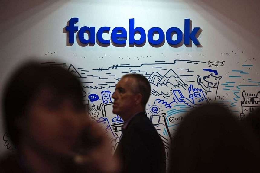People pass by the stand of Facebook during the Web Summit at Parque das Nacoes, Lisbon on Nov 9, 2016.