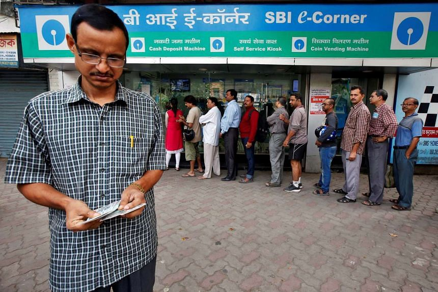 A man counts Indian rupee banknotes after withdrawing them from State Bank of India ATM in Kolkata, India, Nov 11, 2016.