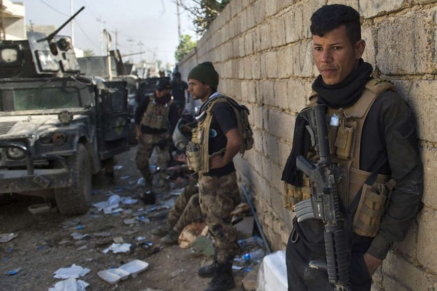 Soldiers from the Iraqi Special Forces take cover before engaging militants in Mosul on Nov 11, 2016.