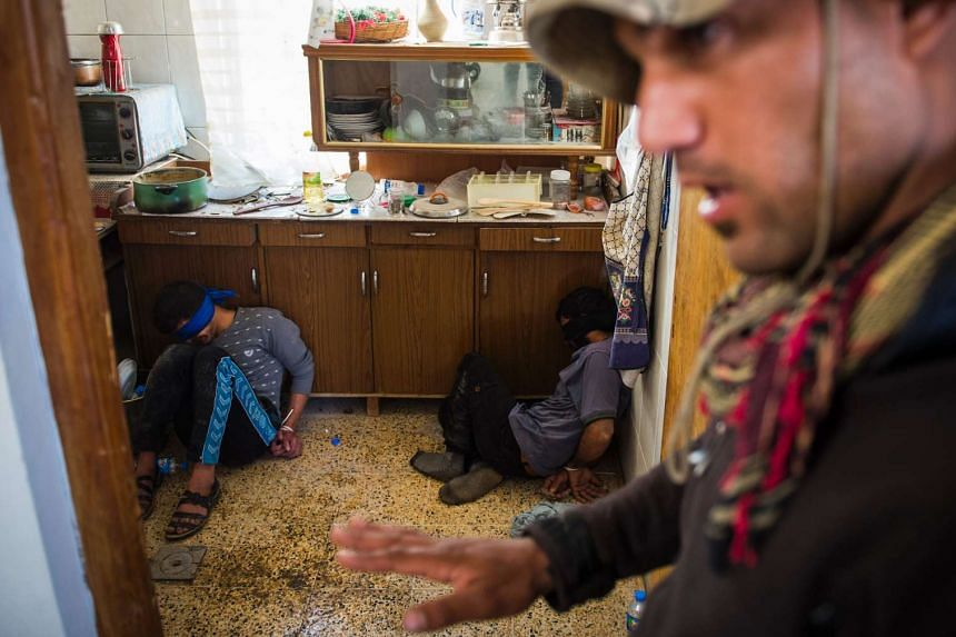 A soldier from the Iraqi Special Forces 2nd division guards two suspected ISIS fighters found hiding in a house as they were pushing through the eastern Samah area.