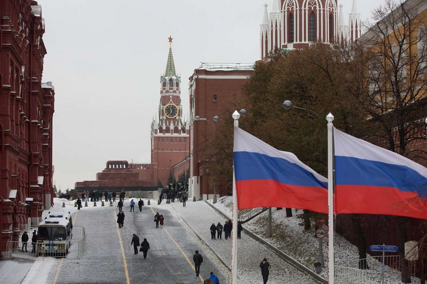 Two Russian Federation flags fly on a road leading to the Lenin mausoleum on Red Square in Moscow, Russia.