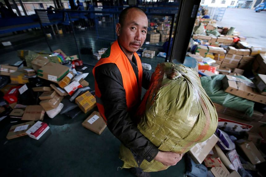 A worker carries parcels at a logistics centre of ZTO Express during the Alibaba 11.11 event, in Beijing, China, Nov 11, 2016.