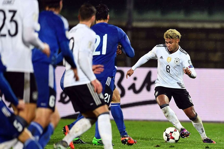 Germany's midfielder Serge Gnabry (right) runs with the ball during the World Cup 2018 qualifying football match between San Marino and Germany.
