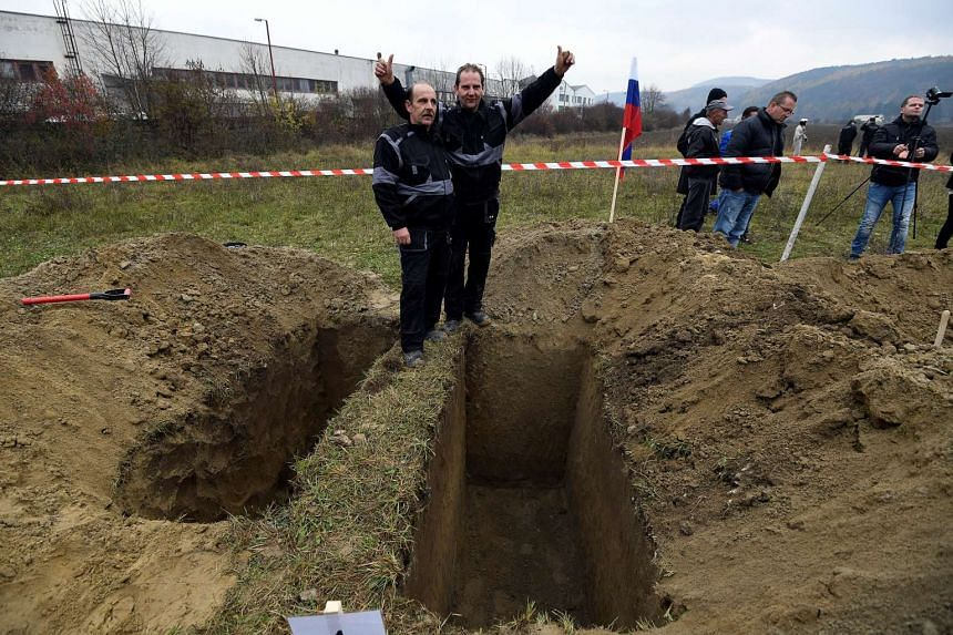Brothers Ladislav (left) and Csaba Skladan from Slovakia won a grave-digging championship in Trencin, Slovakia, on Thursday where contestants were assessed on accuracy, speed and aesthetic quality.