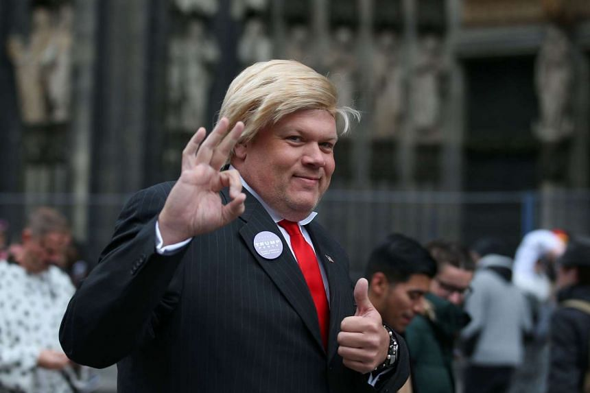 A reveller dressed as Donald Trump gestures at the start of the Carnival season on Nov 11, 2016, in Cologne, western Germany.