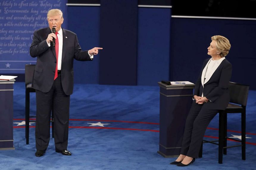 Republican US presidential nominee Donald Trump speaking as Democratic US presidential nominee Hillary Clinton listens during their presidential town hall debate at Washington University on Oct 9, 2016.