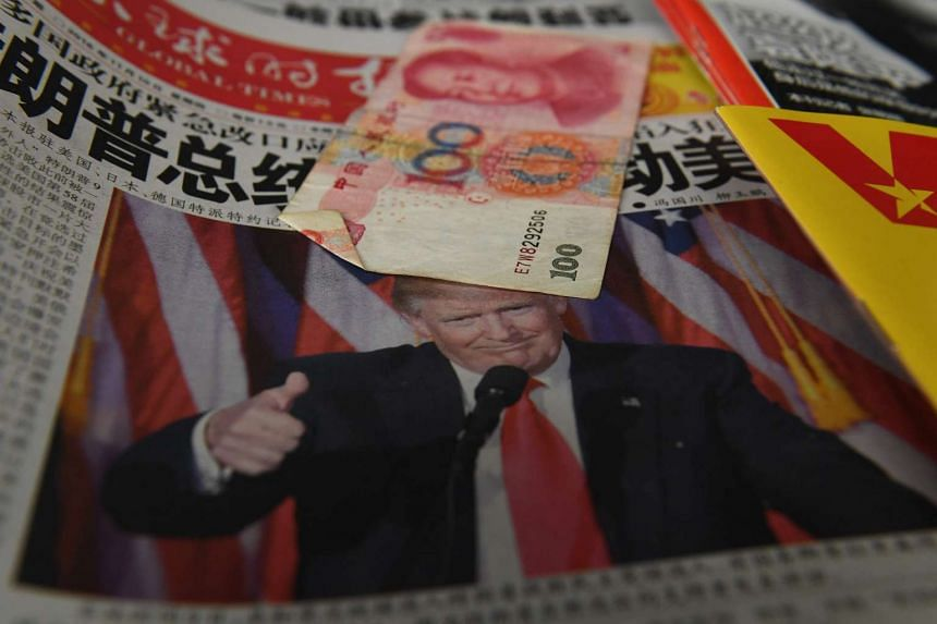 "A Chinese newspaper featuring a photo of US President-elect Donald Trump that reads ""President Trump shakes America"", is partially covered by a 100 yuan note on a news stand, as a customer (not pictured) waits to buy a phone card in Beijing, on Nov 1"
