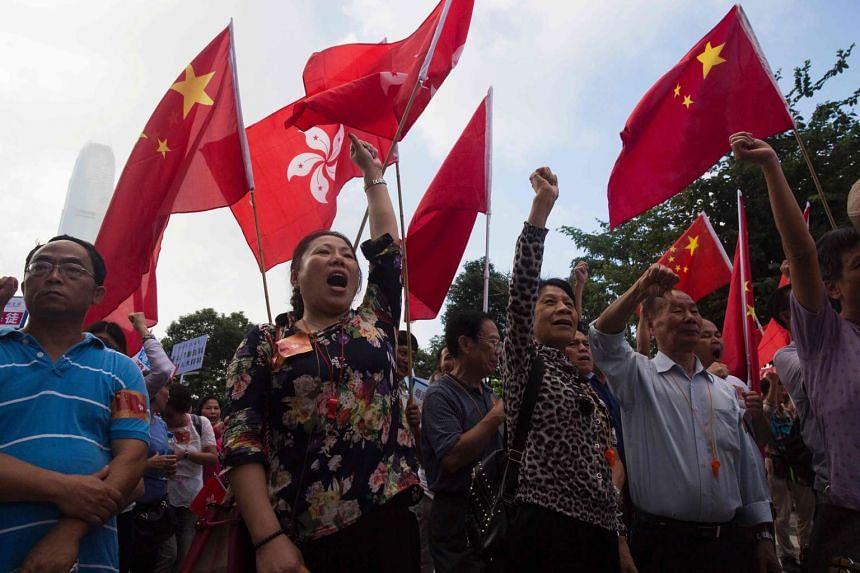 Pro-Beijing demonstrators shout slogans and wave flags outside the Hong Kong Legislative Council on Nov 13, 2016.