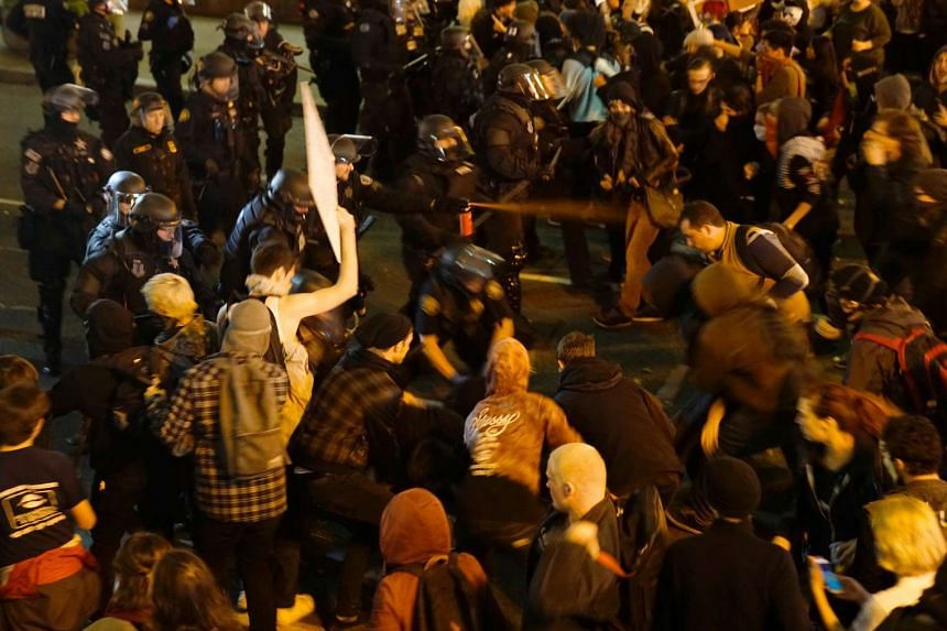 A police officer sprays the crowd with an irritant during an anti-Trump protest in Portland, Oregon, Nov 12, 2016.