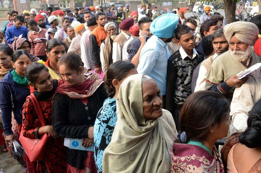 Indian villagers queue outside a bank as they wait to deposit and exchange 500 and 1000 rupee notes at Khasa village, some 20km from Amritsar on Nov 12, 2016.