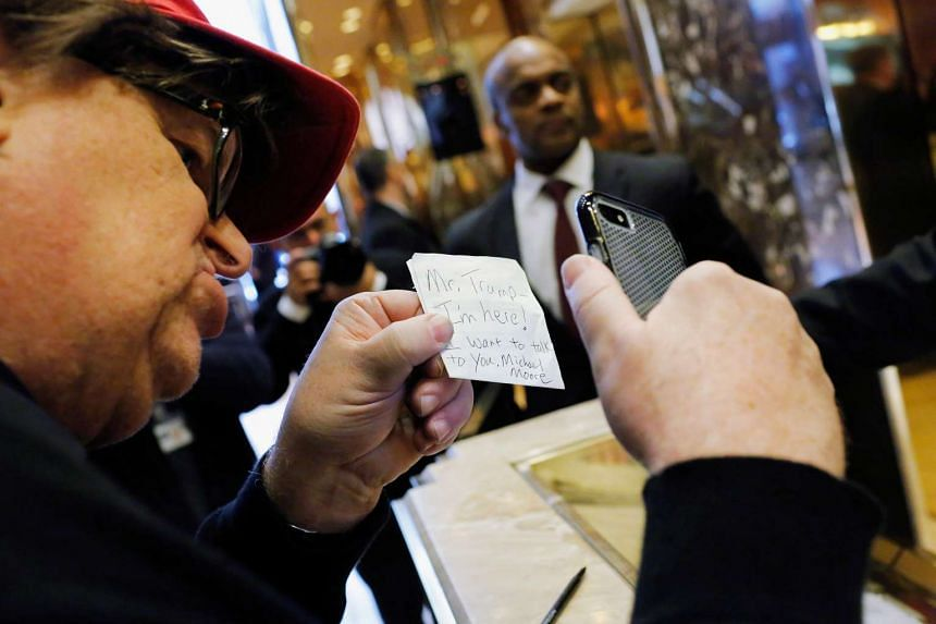 Filmmaker Michael Moore leaves a note for Donald Trump as he visits Trump Tower in New York.