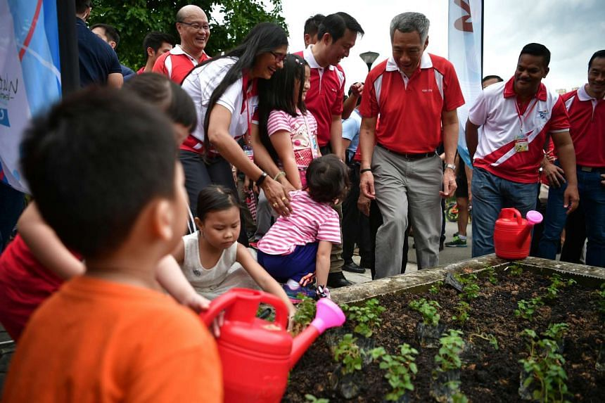 Prime Minister Lee Hsien Loong mingles with children and their families as they plant small plants at Punggol Reservoir during the Ang Mo Kio GRC and Sengkang West SMC Tree Planting event on Nov 13, 2016.