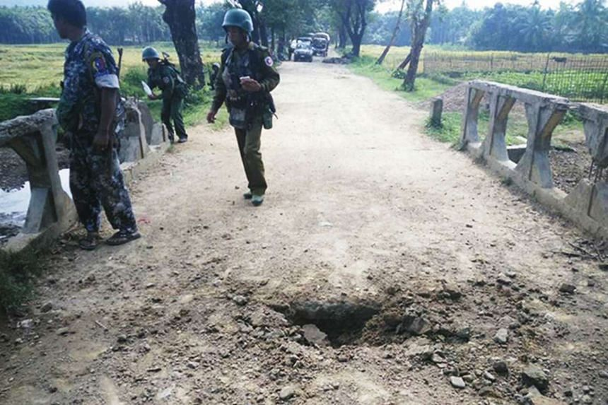 A handout photo from the Myanmar Armed Forces shows soldiers viewing the crater from a landmine explosion on a bridge in Maung Nama Taung village, located in Rakhine state, on Nov 12, 2016.