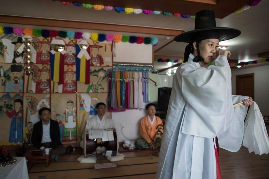 Shaman Lee Won Bok (right) performs a ritual at a shamanic centre in Yangju, north of Seoul, on Nov 8, 2016.