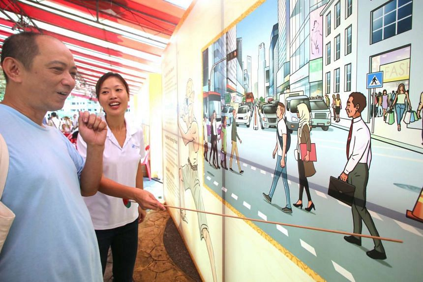 An attendee looks at a display at the Traffic Police's booth during the Bedok Community for All Ages Day.