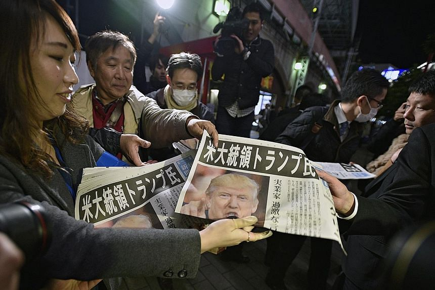 Newspapers reporting Mr Trump's election win being distributed in Tokyo. Mr Trump will meet Japanese Prime Minister Shinzo Abe in New York on Thursday.