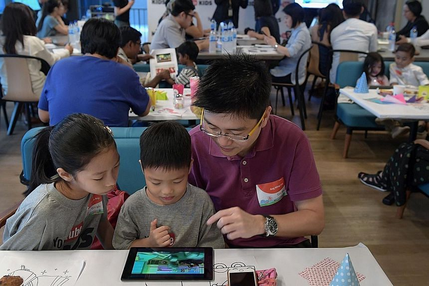 Sales manager Ang Wing Lai, 45, and his children Nicole, nine, and Jonas, four, checking out YouTube Kids during the app's launch yesterday at Google Asia-Pacific's new office at Mapletree Business City II.
