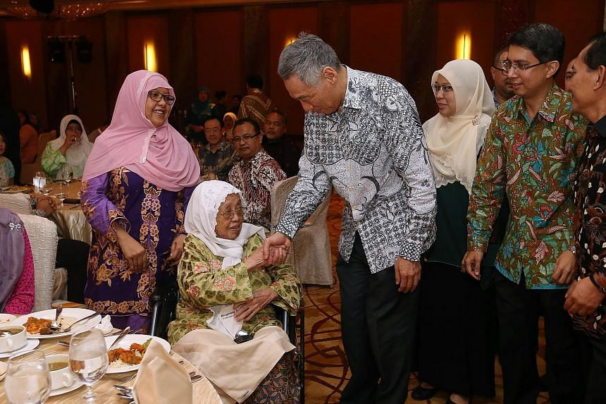 PM Lee presenting a token of appreciation to the late veteran writer Muhammad Ariff Ahmad's wife Sarinah Haniff as her daughter Shahrulbariah (left) looks on at the Arif Budiman Malay Language Teachers' Award ceremony yesterday. Behind PM Lee are Ang