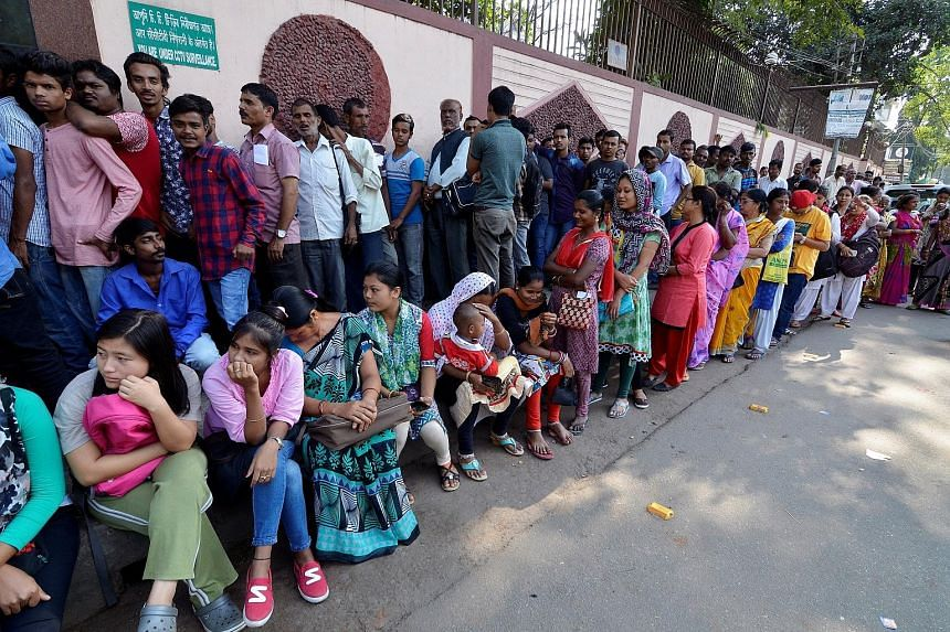 Indians waiting in queue outside a bank in Guwahati yesterday to exchange 500- and 1,000-rupee notes that were taken out of circulation last week in a shock move aimed at uncovering unaccounted wealth hidden from the taxman.