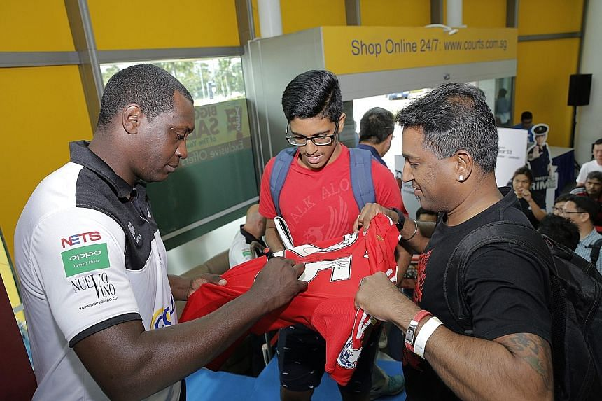 Straits Times reader Vijayarengan Visvalingam with his nephew Morhan Ramasamy getting a jersey signed by former England and Liverpool player Emile Heskey at the Courts Megastore in Tampines yesterday. Heskey was at the store to meet and greet fans al