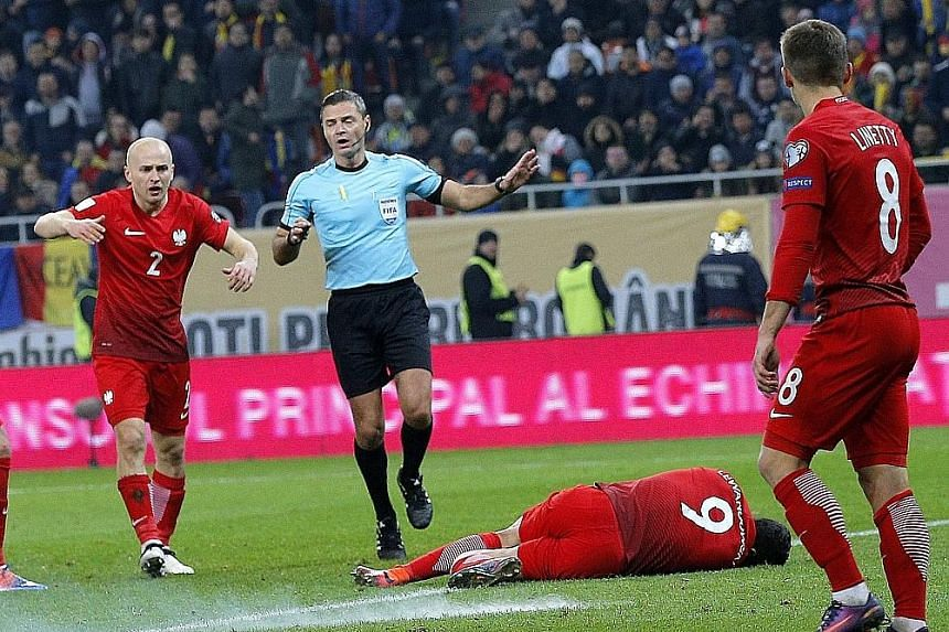 Poland captain Robert Lewandowski lies on the pitch in Bucharest after a firecracker thrown by Romanian supporters exploded about a metre away from him during the World Cup qualifier on Friday. After receiving medical treatment, he was cleared to con