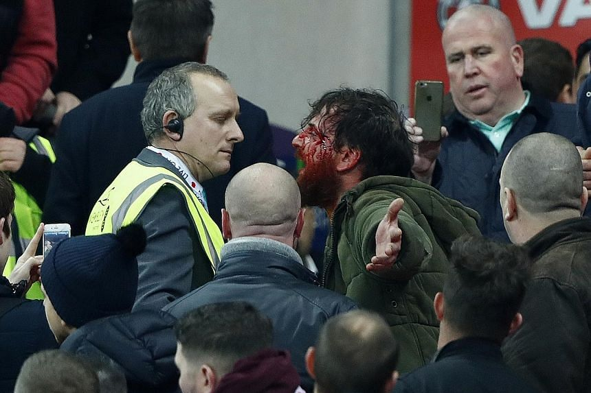 A bloodied fan arguing with a steward as England and Scotland supporters clash during the game at Wembley. A fine is probably the more likely outcome instead of point deductions, which will scarcely hurt leaders England.