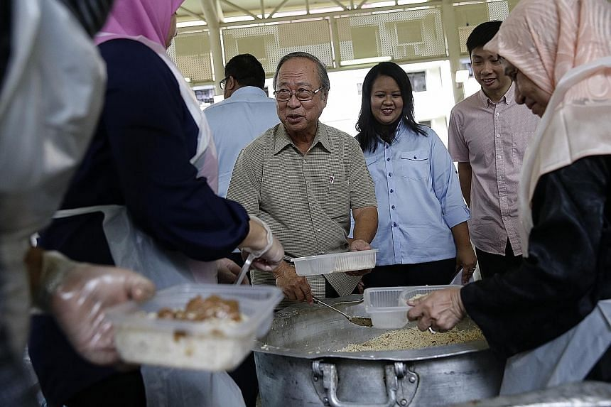 Dr Tan attending a charity event by Free Food For All in Chai Chee yesterday. He said he will not retreat from the public eye and will still help Singapore.