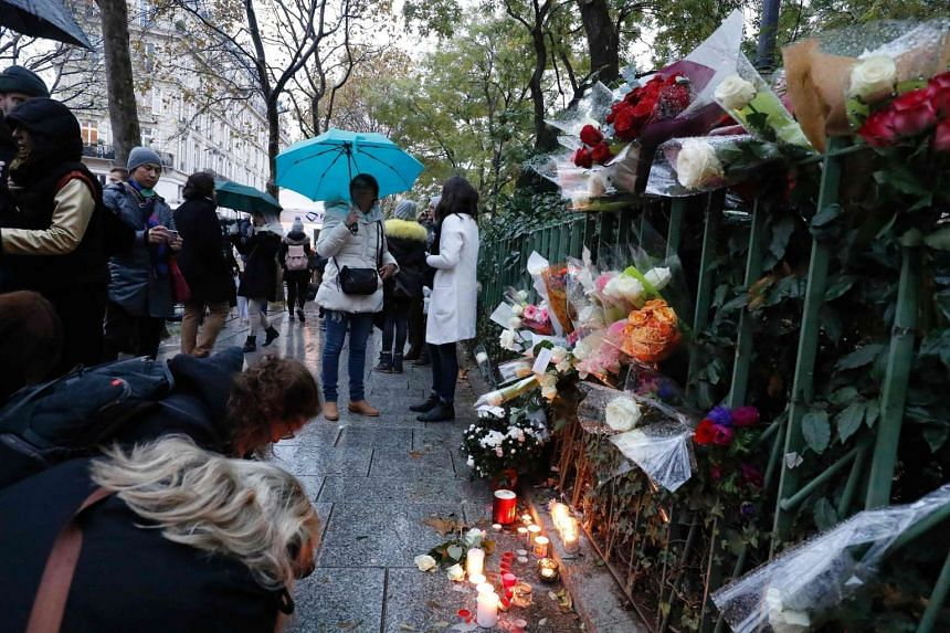 People gather around flowes and candles laid next to the Bataclan concert hall in Paris before it reopened on Nov 12, 2016.