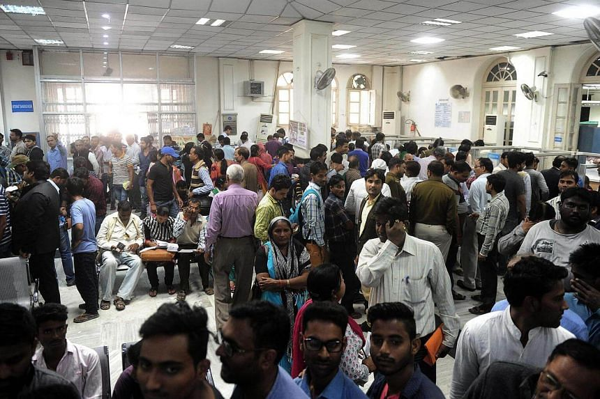 Indian people queue inside a bank as they wait to deposit and exchange 500 and 1000 INR notes, in Allahabad on Nov 12, 2016.