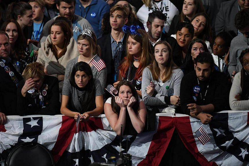 Glum-looking Hillary Clinton supporters watch results roll in from the states on election night.