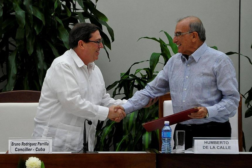 Cuban Foreign Affairs Minister Bruno Rodriguez Parrilla (left) and the head of the Colombian government's delegation for peace talks with the FARC, Humberto de la Calle, shake hands after the signing of a new peace agreement in Havana, on Nov 12, 201