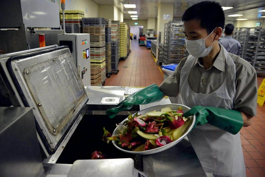 A worker is using a machine to recycle food waste.