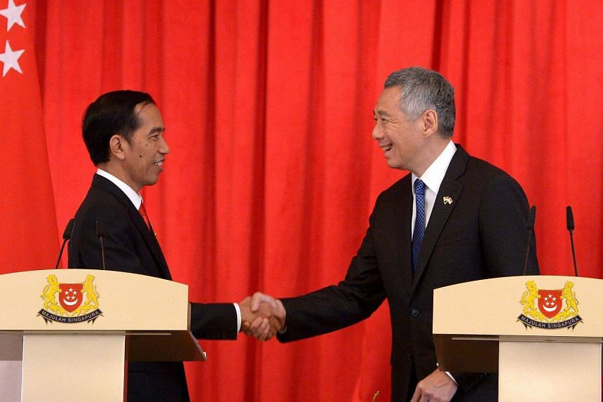 Prime Minister Lee Hsien Loong shakes hands with Indonesia President Joko Widodo after a joint news conference at the Istana in Singapore on July 28, 2015.