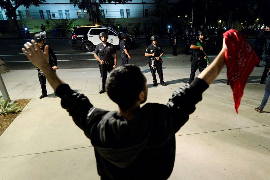 A protester holds up his hands as police look on, after a dispersal order was ignored by anti-Trump demonstrators in Los Angeles, Nov 12, 2016.