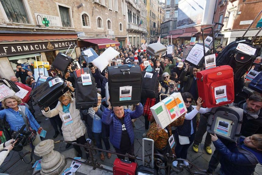 People hold suitcases to protest against an exodus of residents from the city.