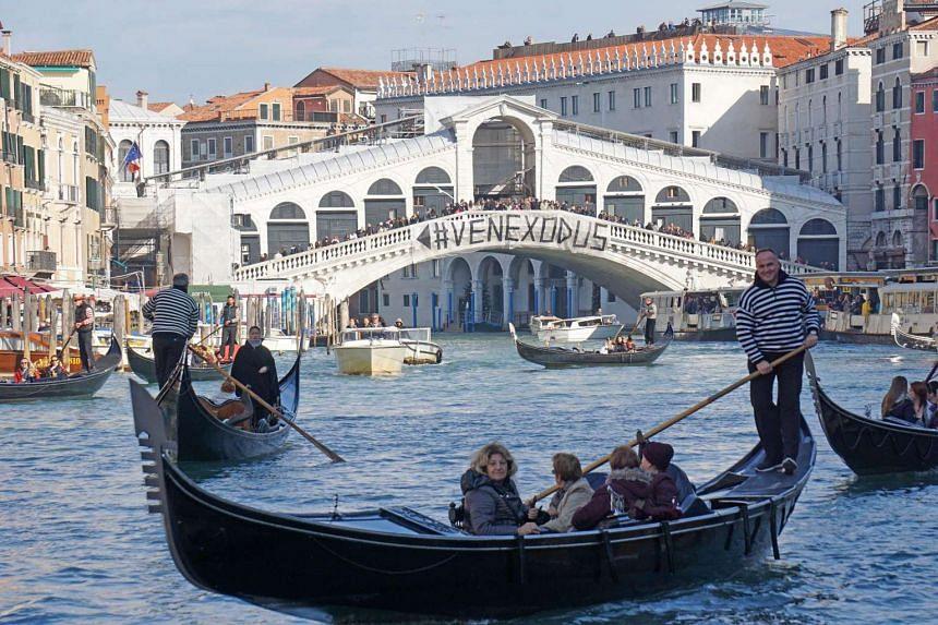 A banner reading Venexodus hangs on the Rialto Bridge in Venice, Italy, Nov 12, 2016.