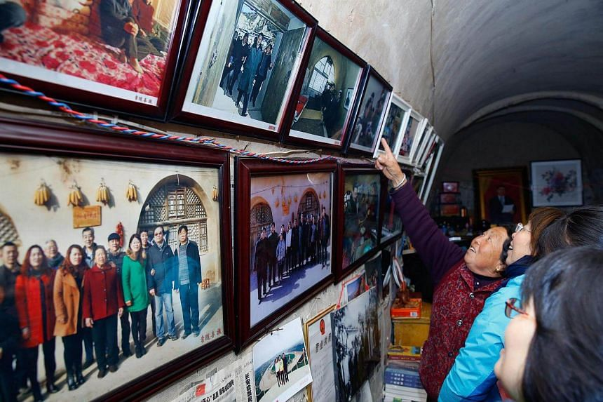 Visitors looking at photos of China President Xi Jinping in the cave home in Liangjiahe, Shaanxi province, where he lived as a youth.
