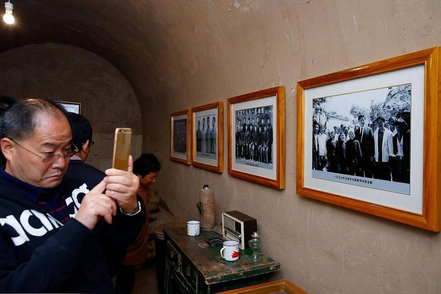A man taking photos in Mr Xi's cave home.