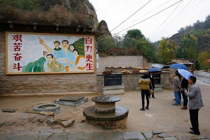 A mural extolling hard struggle outside Mr Xi's cave home.
